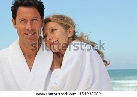 couple in bathrobes on the beach - stock photo
