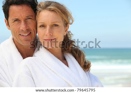 Couple in bathrobes on the beach - stock photo