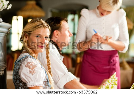Couple in Bavarian Restaurant ordering food and drinks from the waitress