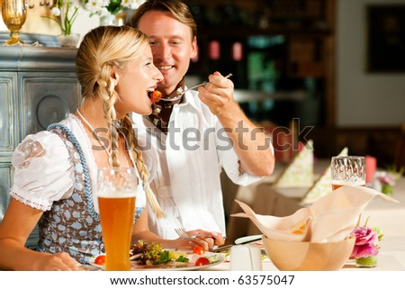 Couple in Bavarian restaurant, wearing Tracht eating Wurstsalat and having wheat beer glasses in the table - stock photo