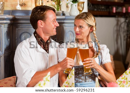 Couple in Bavarian Tracht drinking wheat beer in a typical pub, clinking classes - stock photo