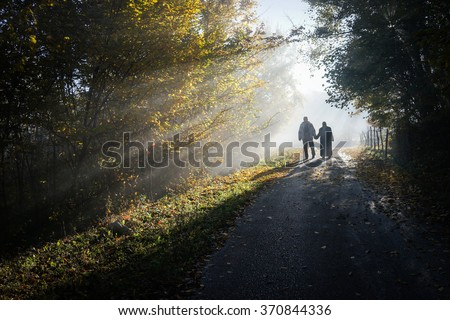 Couple in beautiful foggy and sunny mysterious nature