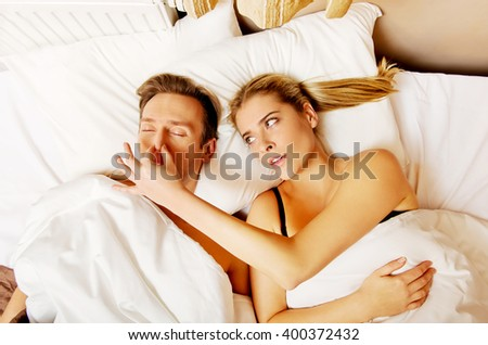Couple in bed,man snoring woman can't sleep - stock photo