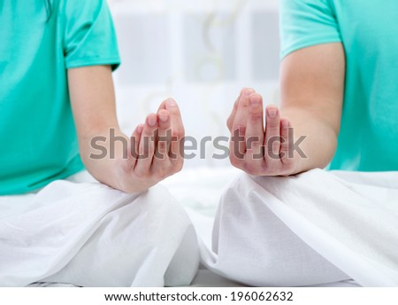 couple in bed together meditating  - stock photo