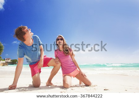 couple in bright clothes enjoying sunny day at tropical beach