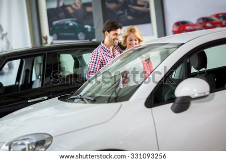 Couple in  car dealership saloon looking for a new car - stock photo