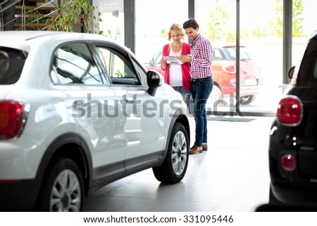 couple  in car showroom reading brochure and choosing new car  - stock photo