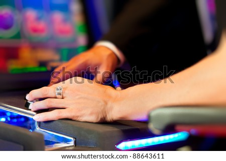 Couple in Casino on a slot machine winning and having fun - only hands to be seen - stock photo