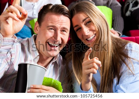 Couple in cinema watching a movie, it seems to be a funny movie - stock photo
