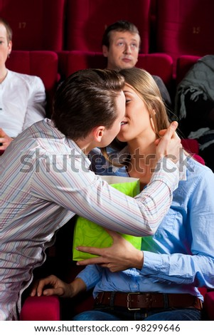 Couple in cinema watching a movie, they eating popcorn and kissing - stock photo