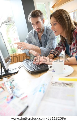 Couple in coffee shop websurfing on desktop computer - stock photo