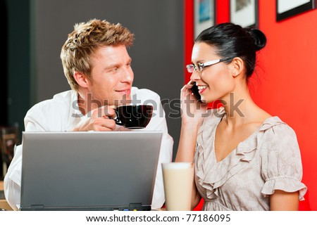 Couple in coffeeshop with laptop and mobile; obviously they are working - stock photo