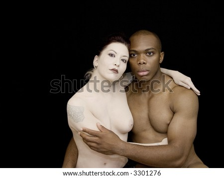 Couple in contrast arms around each other, bare chested. - stock photo