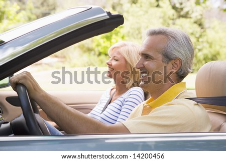 Couple in convertible car smiling - stock photo