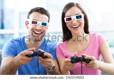 Couple in 3d glasses playing video games - stock photo