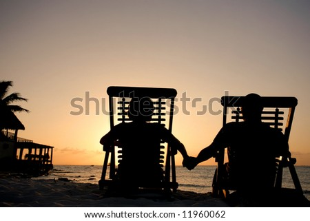 Couple in deckchairs holding hands at sunset - stock photo