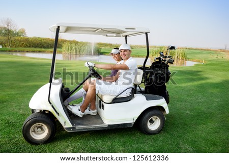 Couple in  driving buggy on golf course - stock photo