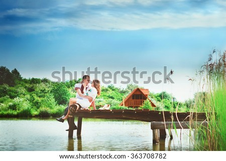 couple in embroidered shirts hug sitting on the dock at the lake