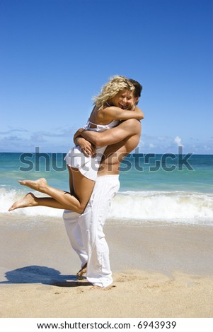 Couple in emotional embrace on Maui, Hawaii beach.