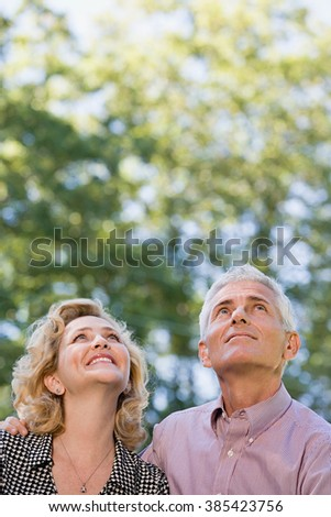 Couple in forest looking up