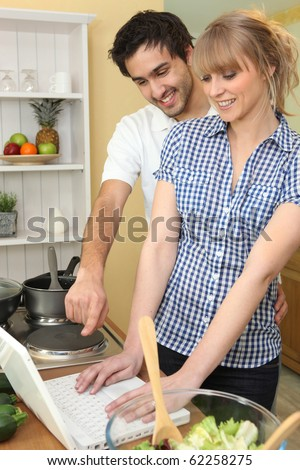 Couple in front of a laptop computer in the kitchen