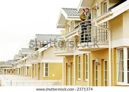 couple in front of one-family house in modern residential area