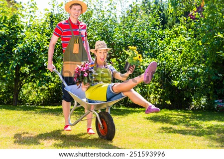 Couple in garden with watering can and barrow - stock photo