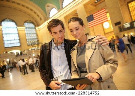 Couple in Grand Central station looking at train departure time - stock photo