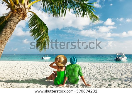 Couple in green clothes on a tropical beach at Maldives