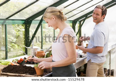 Couple in greenhouse putting soil in pots smiling - stock photo