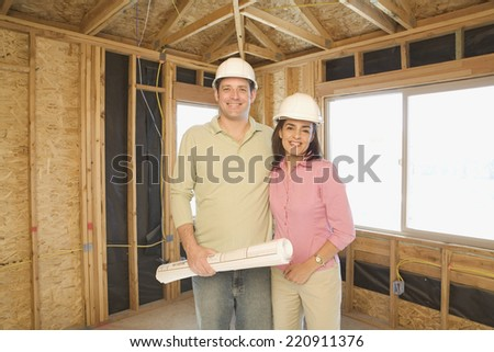 Couple in hard hats with blueprints on construction site - stock photo