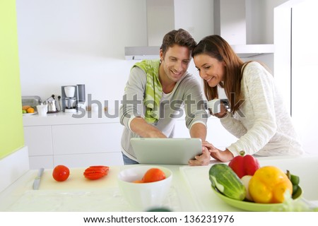 Couple in home kitchen looking for lunch recipe - stock photo