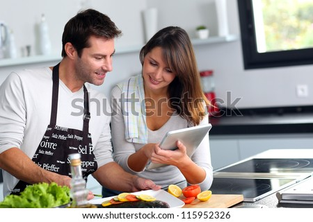 Couple in home kitchen using electronic tablet - stock photo