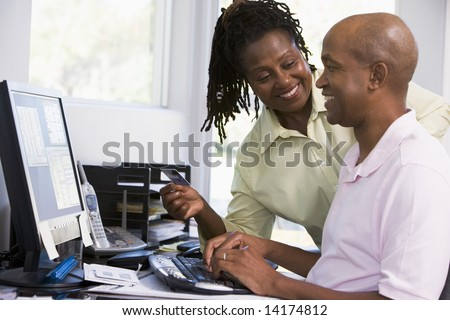 Couple in home office with credit card using computer and smiling - stock photo