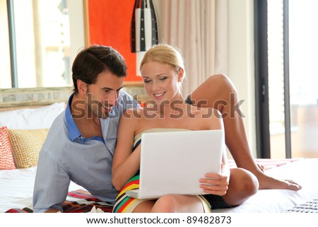 Couple in hotel room connected on internet - stock photo