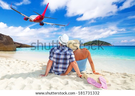 Couple in hug on the beach watching flying aircraft - stock photo