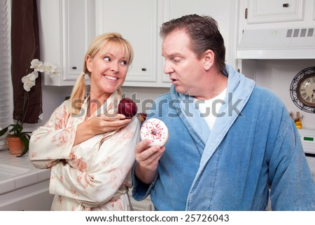 Couple in Kitchen Eating Donut and Coffee or Healthy Fruit. - stock photo