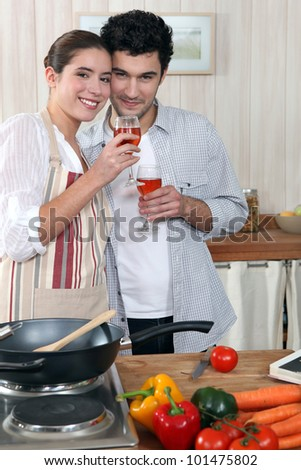 Couple in kitchen with glass of wine - stock photo