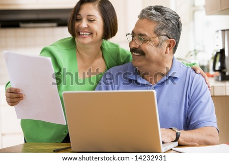 Couple in kitchen with laptop and paperwork smiling - stock photo
