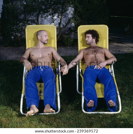 Couple in Lawn Chairs Holding Hands - stock photo