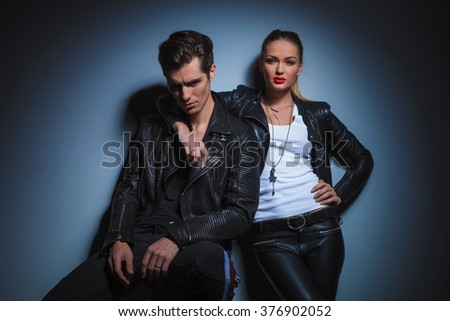 couple in leather jackets posing in studio background. seated man pose for the camera while woman has her hand around his neck - stock photo