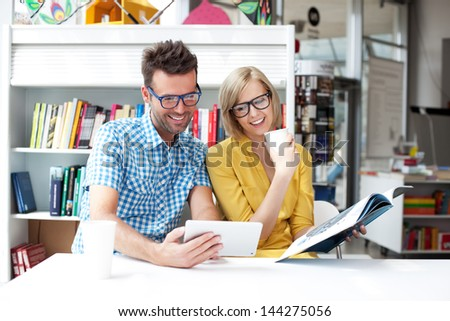 Couple in library working with digital tablet - stock photo