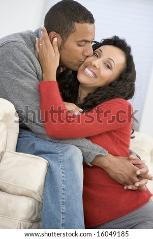 Couple in living room smiling and kissing - stock photo