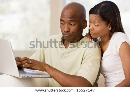 Couple in living room using laptop - stock photo