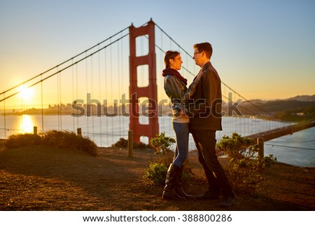 couple in love at the golden gate bridge during sun rise - stock photo