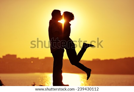 couple in love back light silhouette at lake orange sunset - stock photo