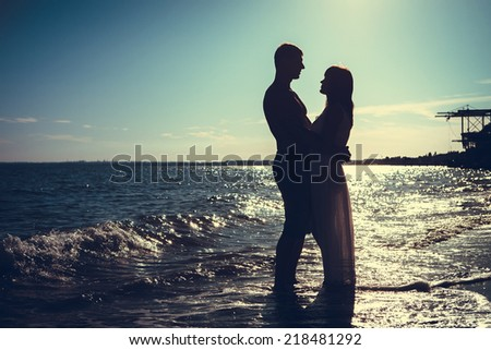 couple in love back light silhouette at sea - stock photo