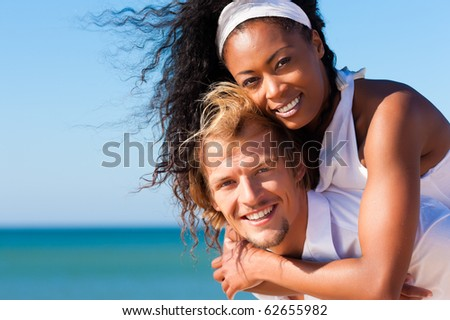 Couple in love - Caucasian man having his African-American woman piggyback on his back under a blue sky on a beach - stock photo