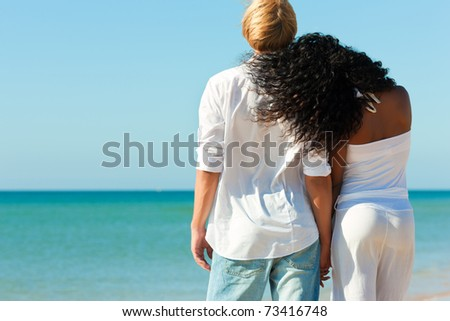 Couple in love - Caucasian man having his African-American woman under a blue sky on a beach - stock photo