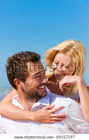Couple in love - Caucasian man having his woman piggyback on his back under a blue sky on a beach - stock photo